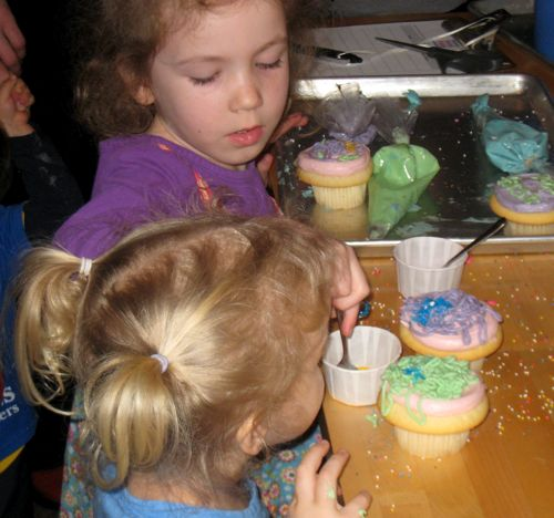 Caitlyn and Raina decorating cupcakes
